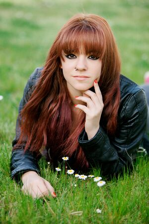 rebellious: Rebellious teenager girl with red hair lying on the grass
