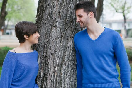 Young lovers dressed in blue supported on a  tree at the park photo