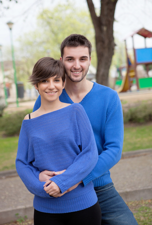 Young lovers dressed in blue looking at camera photo