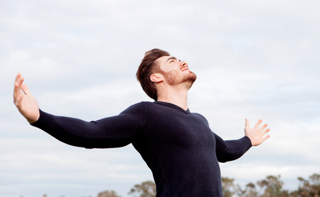 man looking at sky: Handsome guy with open arms relaxed in the field Stock Photo