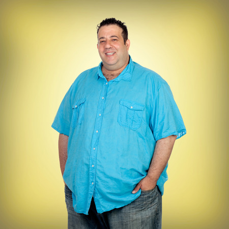 morbidity: Happy fat man with blue shirt and a yellow background Stock Photo