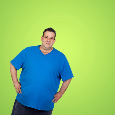potbelly: Happy fat man with blue shirt and a green background Stock Photo
