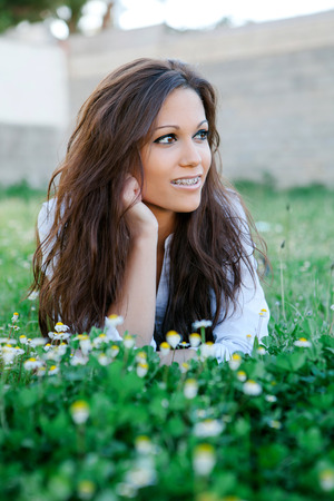 brackets: Brunette cool girl with brackets lying on the grass with many flowers