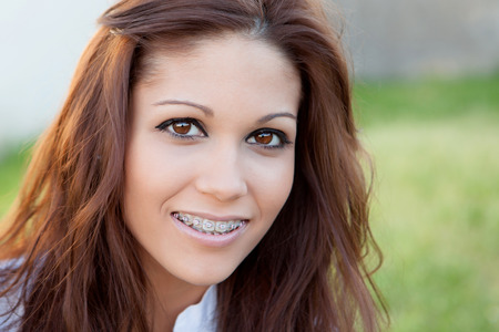 orthodontic: Portrait of a beautiful girl with brackets at the park Stock Photo