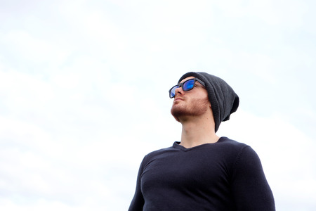 man looking at sky: Handsome cool man with cap wool looking away Stock Photo