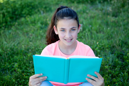 beautiful preteen girl: Beautiful preteen girl with blue eyes reading a book sitting on the grass Stock Photo