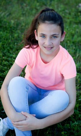 tween: Beautiful preteen girl with blue eyes sitting on the grass Stock Photo