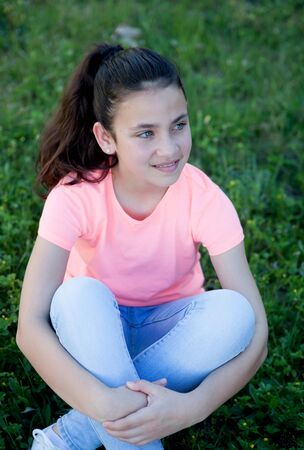 beautiful preteen girl: Beautiful preteen girl with blue eyes sitting on the grass Stock Photo