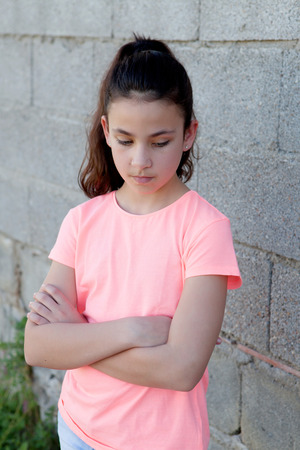 pretty preteen: Angry preteen girl with pink t-shirt in the street