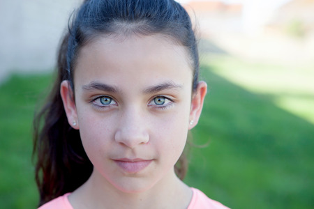 blue eyes girl: Portrait of a beautiful preteen girl with blue eyes outside Stock Photo