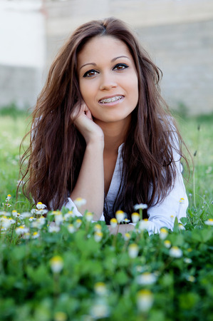 Brunette cool girl with brackets lying on the grass with many flowers photo