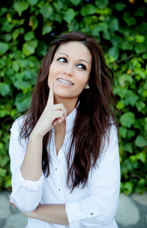 Portrait of a beautiful brunette outdoors in the park thinking photo