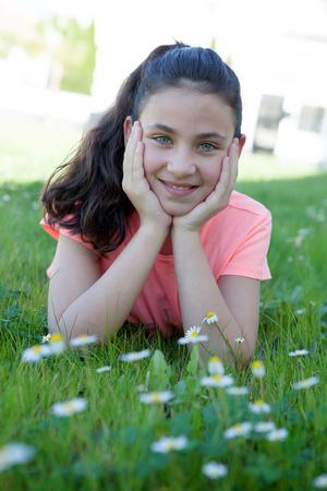 preteen model: Happy casual preteen girl lying in the grass