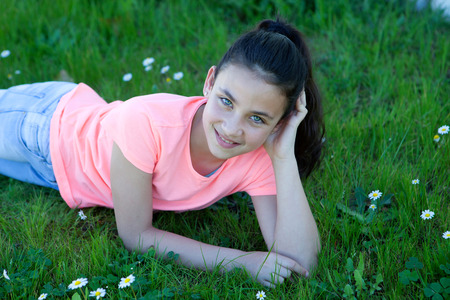 kid friendly: Happy casual preteen girl lying in the grass
