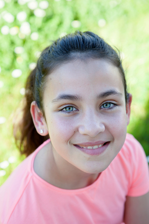 child model: Happy casual preteen girl looking at camera outside Stock Photo
