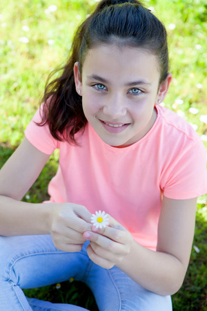 preteen model: Happy casual preteen smelling a daisy at outside Stock Photo