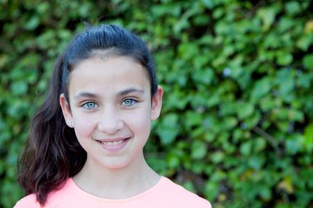 ojos azules: Niña preadolescente feliz con los ojos azules que sonríe en el exterior