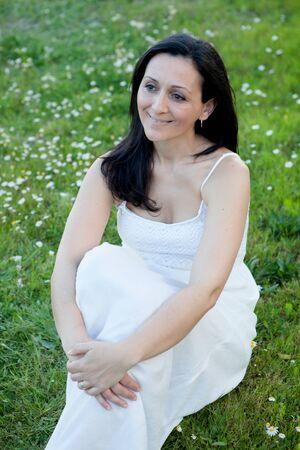 flowered: Brunette woman sitting on a flowered meadow
