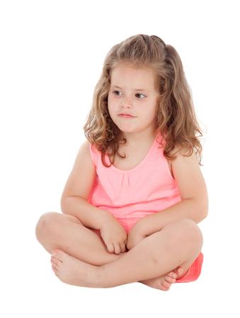 ragazze a piedi nudi: Pensieroso bambina seduta sul pavimento isolato su uno sfondo bianco