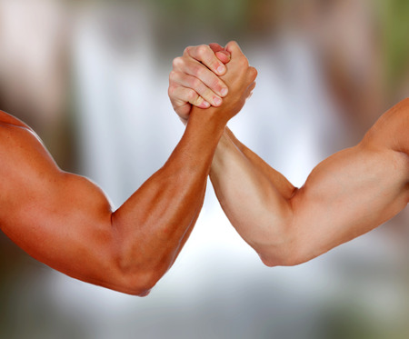 man arm: Strong arms with muscles taking a pulse with a blurred background