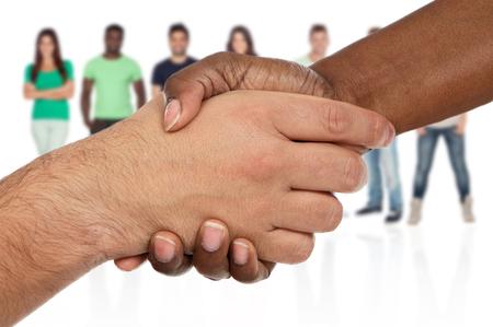 saludo de manos: Apretón de manos entre las razas más de un fondo blanco con la gente fuera de foco de fondo