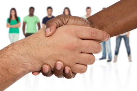 black handshake: Handshake between races a over white background with unfocused people of background Stock Photo
