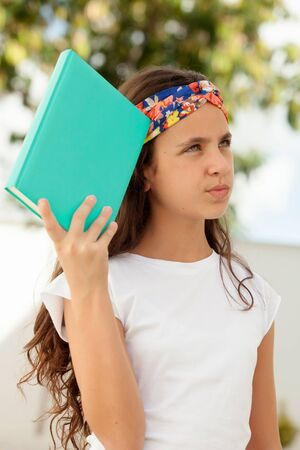 twelve: Pensive Twelve Year Old Student with a book outdoor