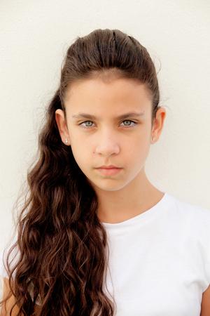 mirada triste: Niña preadolescente enojada con los ojos azules al aire libre Foto de archivo