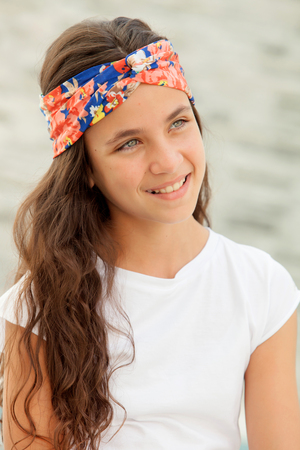 flowered: Pensive teenager girl with a flowered headband smiling outside Stock Photo