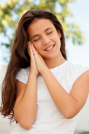 pretty preteen: Pretty young preteen making the symbol of sleep outdoors Stock Photo
