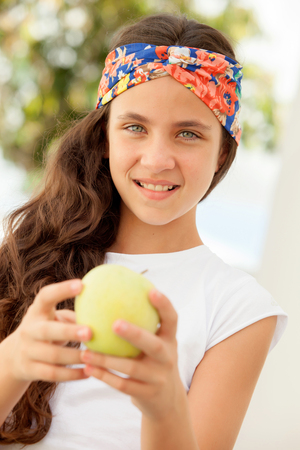 preteen  pure: Teenager girl with blue eyes eating a apple