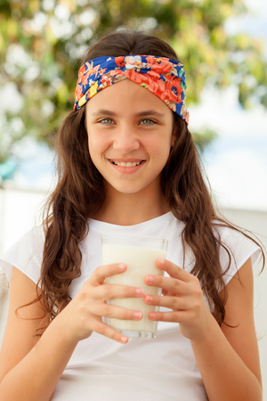 preteen  pure: Teenager girl with blue eyes drinking milk glass