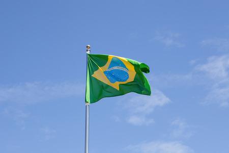 la union hace la fuerza: Bandera brasile�a ondeando en el m�stil con el fondo de cielo azul