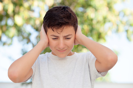 deafening: Sad teenager boy outdoor covering his ears