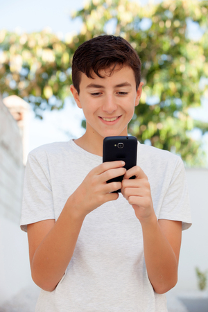 Funny teenage boy looking at the mobile Stock Photo