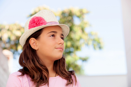 ten year old: Pensive child girl ten year old with a hat on the street