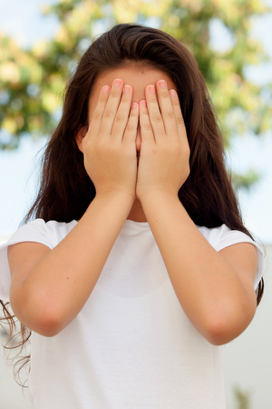 hands covering face: Teenage girl with twelve years old covering her face with the hands