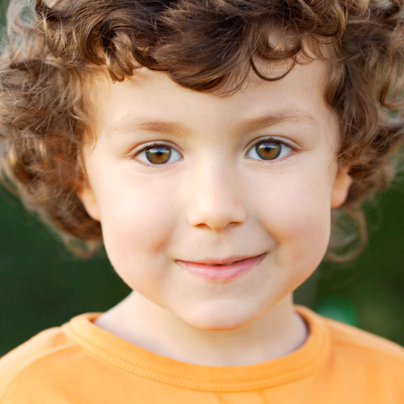 곱슬 머리와 갈색 눈 미소로 어린 소년의 좋은 초상화