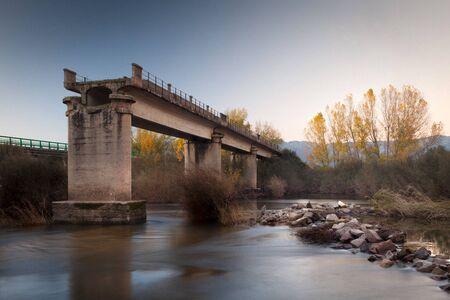 bridging: Broken bridge over a river in autumn