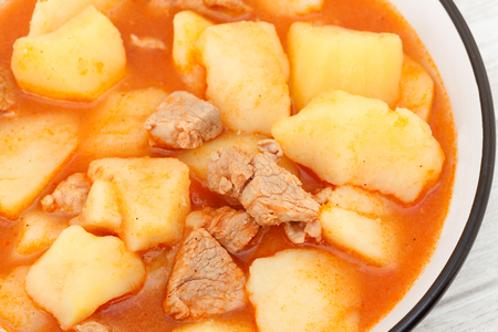 hearty: Hearty beef stew simmering on gray wooden background