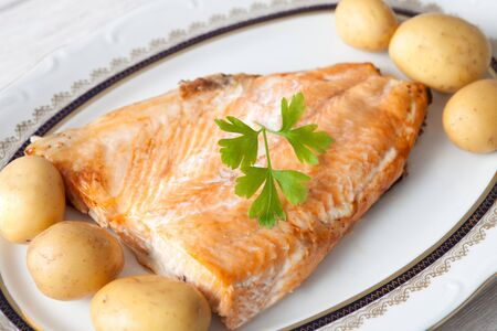 accompanied: Delicious plate of baked salmon accompanied with little potatoes