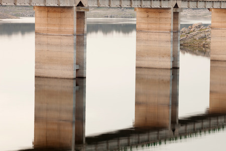 extremadura: Pillars supporting a bridge over the Tagus river in Extremadura, reflected in the water