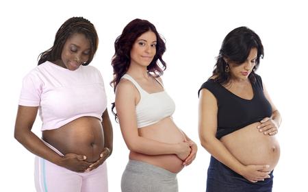 Tres mujeres embarazadas que muestran su vientre aislado en un fondo blanco Foto de archivo