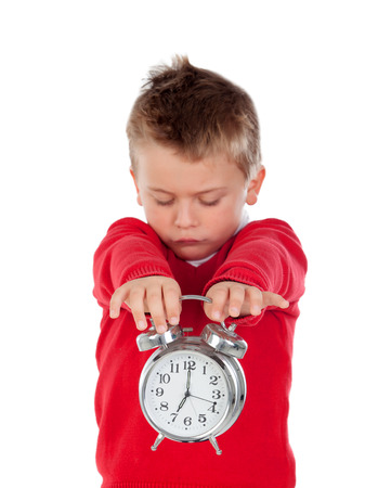 irritate: Angry little boy holding a clock isolated on white background Stock Photo