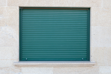 Green closed metal shutter on a window of a stone house Standard-Bild