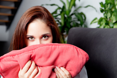 Shy woman hiding her face cushion on the couch at home Stock Photo