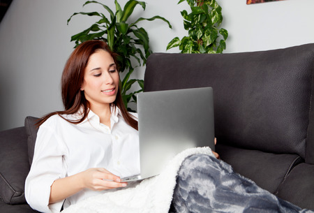 comfortable: Happy young woman is relaxing on comfortable couch and using laptop at home.