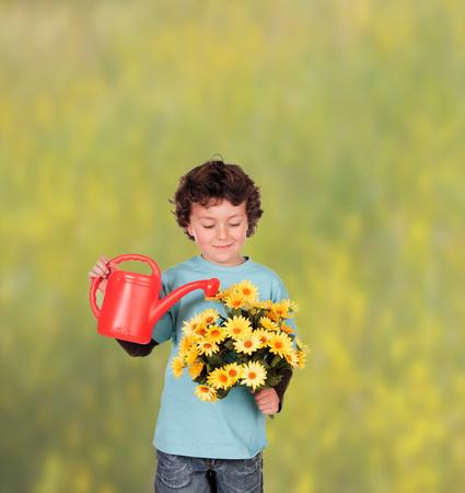 six years: Small six years boy watering some beautiful yellow flowers