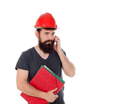 casco rojo: Los hombres jóvenes con mirada inconformista y casco rojo que mira el móvil aislado en el fondo blanco Foto de archivo