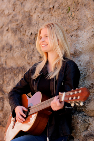 girl playing guitar: Cool blonde girl playing guitar leaning against a stone wall Stock Photo